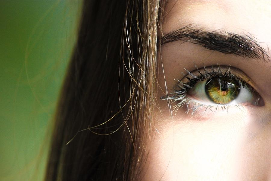 Symbolbild für Jin Shin Jyutsu Augen: Auge einer Frau vor grünem Hintergrund