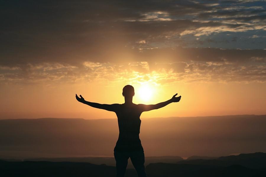 Symbolbild für Jin Shin Jyutsu Corona: Eine Frau steht stark und gesund mit ausgetreckten Armen vor einem Sonnenuntergang