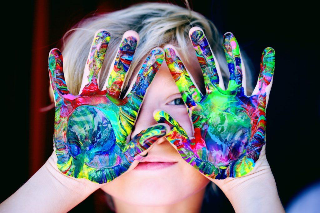 Symbolbild Jin Shin Jyutsu Kinder: Kind hält bunt bemalte Handflächen vors Gesicht
