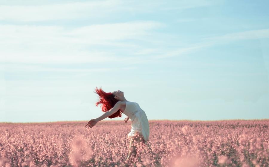 Symbolbild Praxistag Warenhaus der Fülle: Frau steht in einem Feld mit rosa Blumen