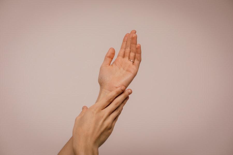 Symbolbild Strömen Jin Shin Jyutsu: eine Frauenhand umfasst ihr Handgelenk